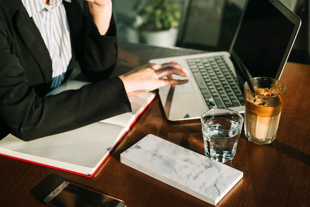 木製の机の上にラップトップを使用している実業家の手のクローズアップ