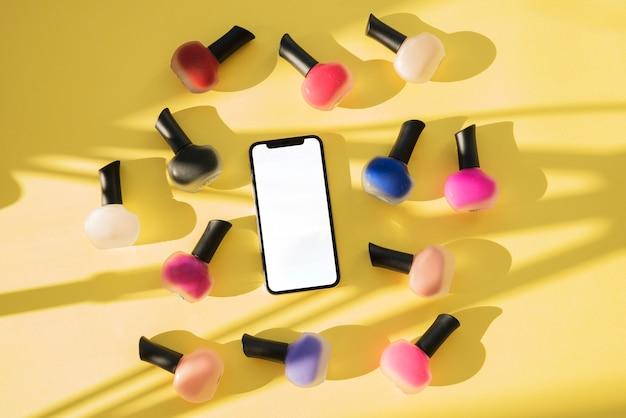 黄色の背景にカラフルなマニキュアを持つスマートフォンのハイアングル