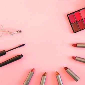 アイシャドウパレット。まつげカーラー。マスカラーとピンクの背景の上の口紅のさまざまな色合い