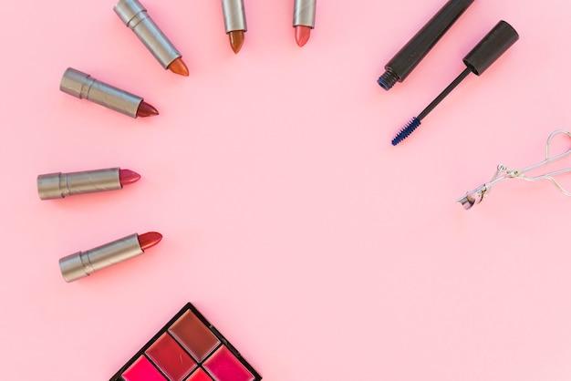 アイシャドウパレット。さまざまな口紅の色合い。マスカラ;ピンクの背景の上に配置