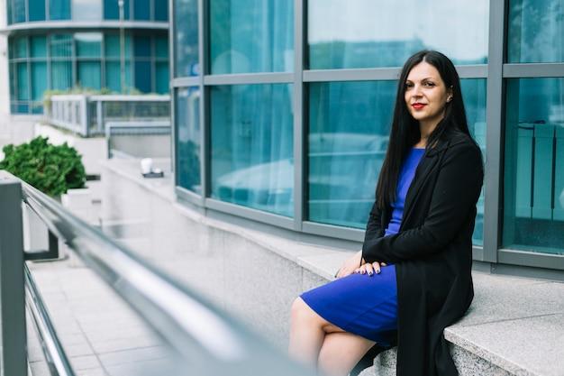 事務所ビルの外に座っている美しい女性実業家の肖像画