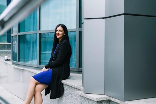カメラ目線の建物の外に座っている若い女性の側面図