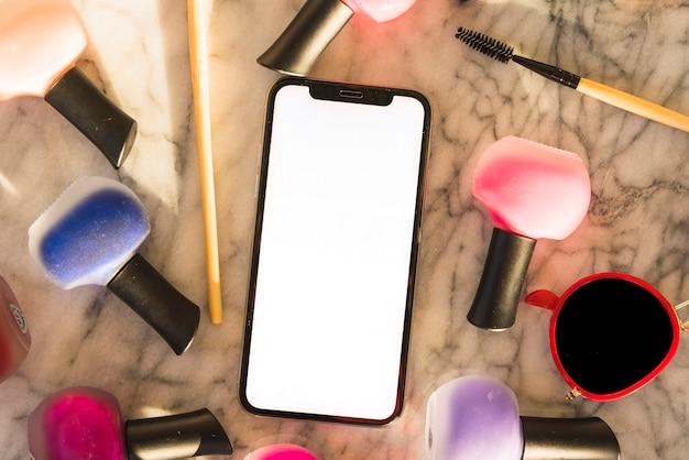 大理石の背景にカラフルなマニキュアとマスカラーを持つスマートフォンの立面図