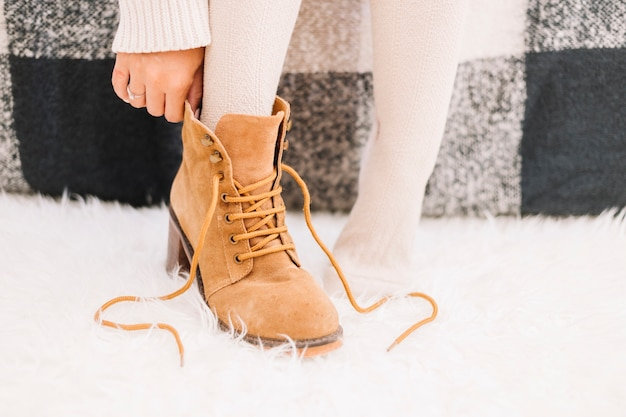 Женщина надевает обувь на