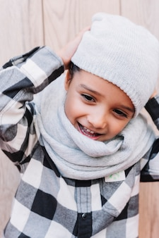 小さな男の子は冬のキャップを置く