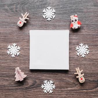 小さいクリスマスのおもちゃを持つ紙