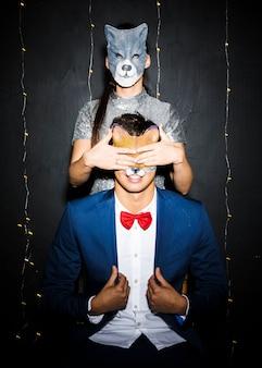 Женщина в маске кошки закрывает глаза мужчине в маске лисы