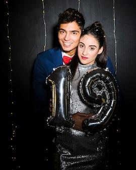 バルーンの数字で魅力的な女性を抱擁する若い男
