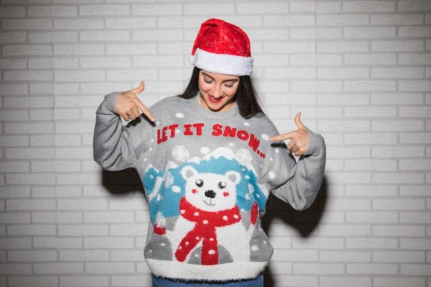 クリスマスの帽子とセーターの若いブルネット女性
