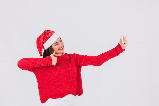 セルフのポーズをとっているクリスマスの帽子のお祝いの女性
