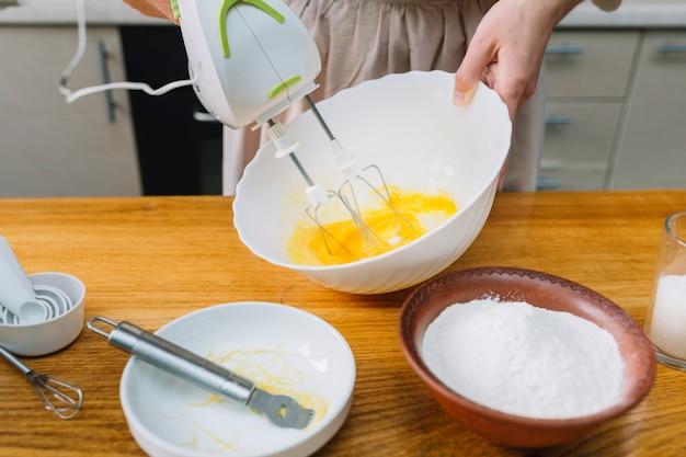 ボウルに卵を混合する女性のクローズアップ