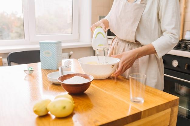 木製の机の上にパイを準備するための原料を混合する女性の中央部