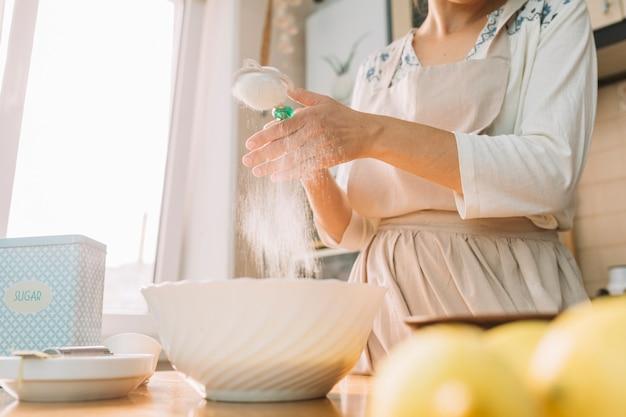 台所で女性の中央部はパイを作るために小麦粉から生地を準備します