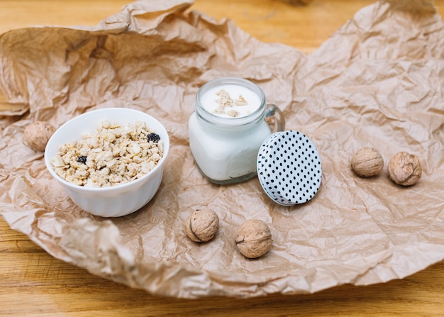 穀物のボウル。ミルクとクルミのしわくちゃの茶色の紙