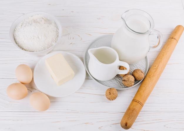 Повышенный вид муки; молоко; яйца; сыр и грецкие орехи на белом деревянном столе для приготовления пирога