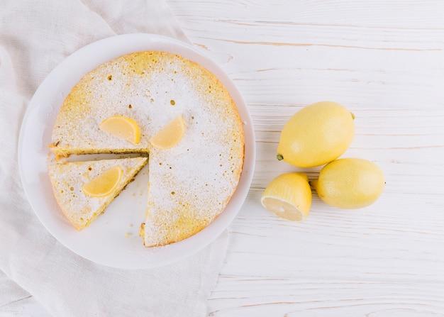 木製のテーブルに飾られた丸いレモンケーキとレモンの立面図
