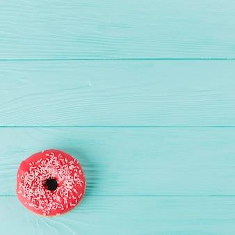 木製のテーブルの上の振りかけると新鮮なドーナツ
