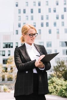 ペンでクリップボードに書き込むスーツの女性実業家