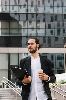 クリップボードとコーヒーカップを保持している建物の前に立っている自信がある実業家