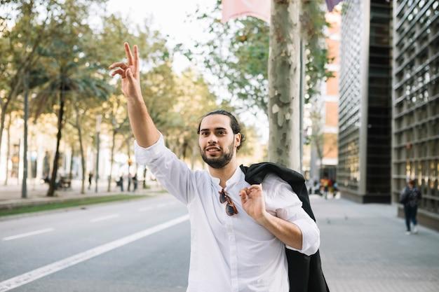Бизнесмен пытается поймать такси на улице города
