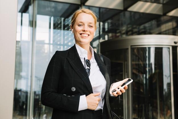 Уверен, улыбающийся молодая женщина, держащая мобильный телефон в руке