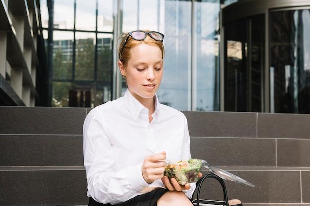Молодая коммерсантка сидя вне офиса есть коробку для завтрака
