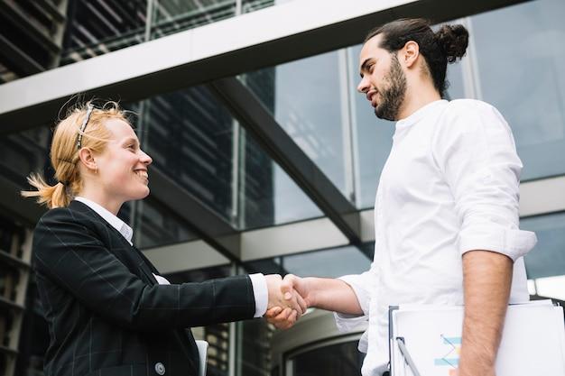 Двое бизнесменов стоят возле офисного здания и пожимают друг другу руки