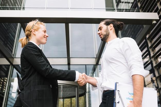 Низкий угол зрения бизнесмена и бизнесвумен, пожимая друг другу руки