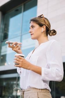 拡声器付きのスマートフォンで話している若い女性の笑みを浮かべてください。