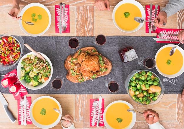お祝いのテーブルでスープを食べる人