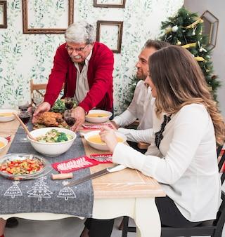老人、ローストチキンをクリスマステーブルに置く