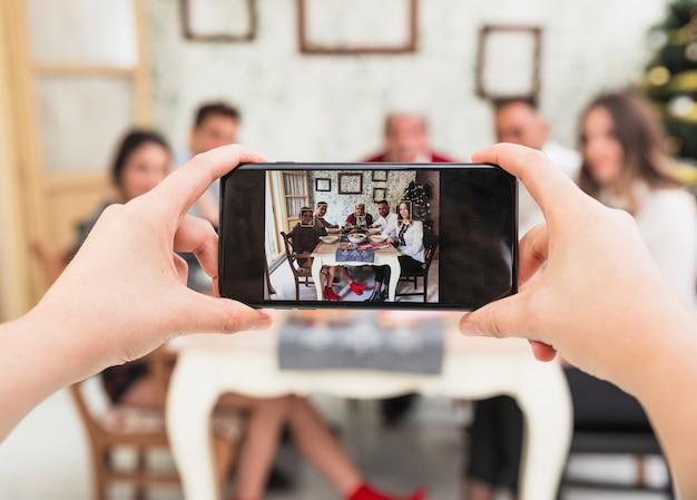 お祝いのテーブルで家族の写真を撮っている人