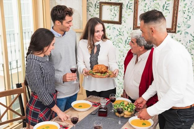 お祝いのテーブルで焼いた鶏を持つ女性
