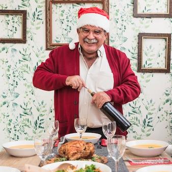 お祝いのテーブルでワインボトルを開く老人