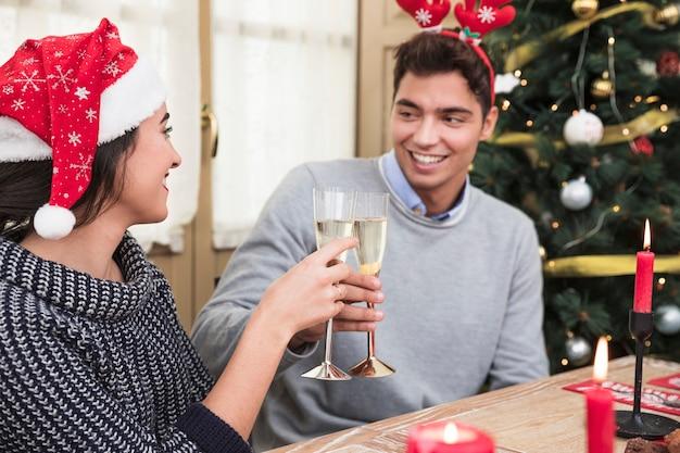 お祝いのテーブルでメガネを握ってカップル