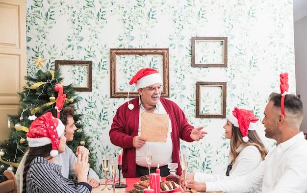 お祝いのテーブルで紙から読む老人
