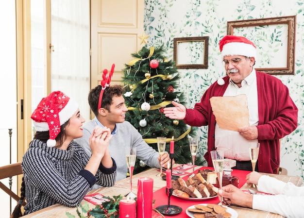 クリスマステーブルで紙から読書する老人