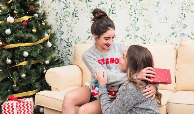 クリスマスツリーの近くのソファーで抱擁する女性
