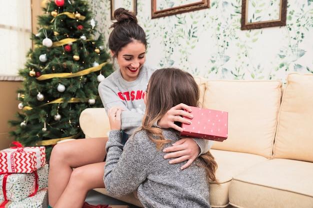 緑のクリスマスツリーの近くのソファで抱擁する女性