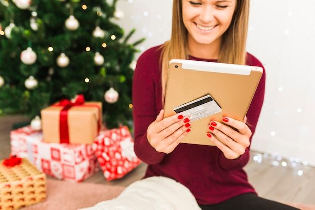 ギフトボックスとクリスマスツリーの近くにタブレットとプラスチックカードで幸せな女性