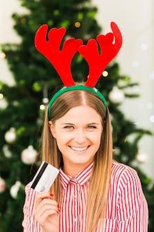 Счастливый женщина с пластиковой картой в оленьих рожках оголовье возле елки