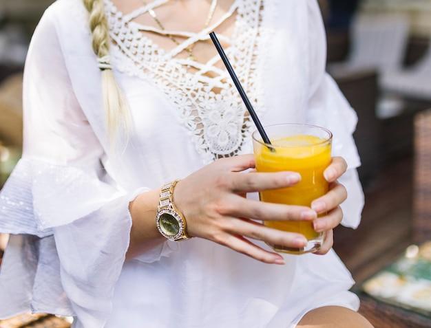 健康ジュースのガラスを保持している白いドレスを着た女性のクローズアップ