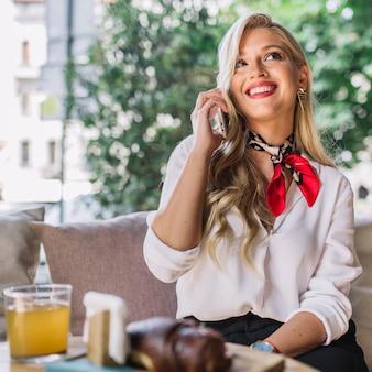 Счастливая белокурая молодая женщина сидя в кафе говоря на мобильном телефоне