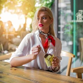 カフェでスプーンでマフィンを食べる思いやりのある若い女性