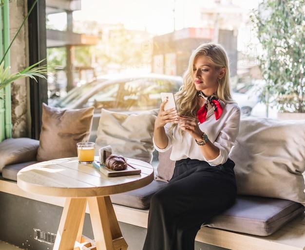 携帯電話を使用してカフェに座っているスタイリッシュな若い女性