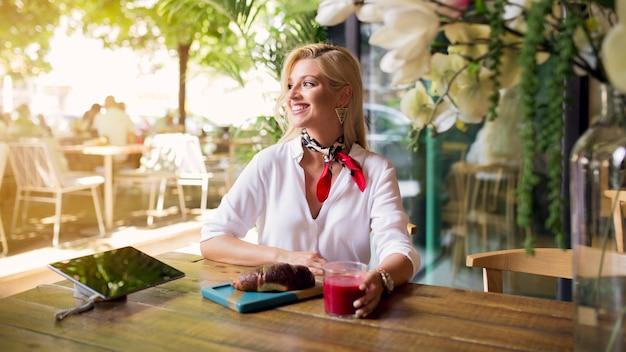 レストランでドリンクやパンを楽しむ若い女性の笑みを浮かべてください。