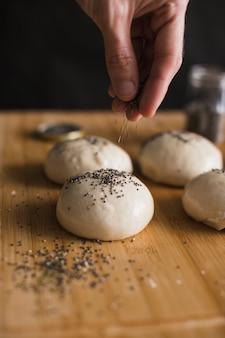未調理のパンの上にチアシードを追加する人の手のクローズアップ