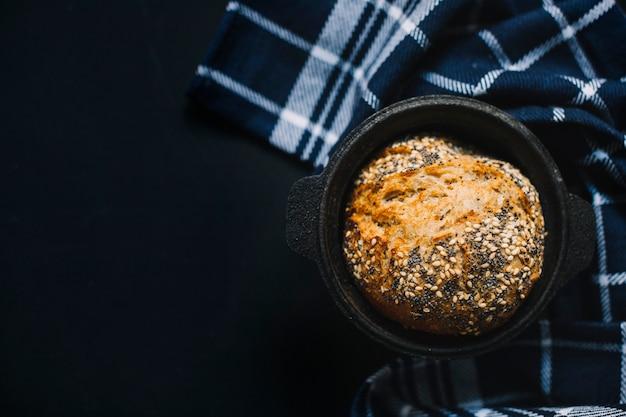 黒の背景に黒のコンテナー内の種子と全粒小麦パン