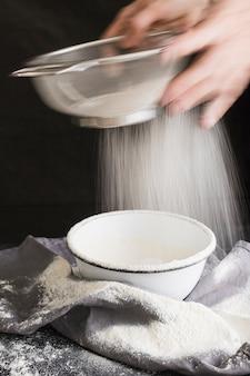 ボウルにふるいで小麦粉をふるいにかける高齢者の女性の手のスローモーション撮影