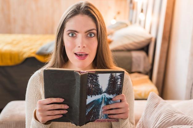 本を手に持って驚いたの若い女性